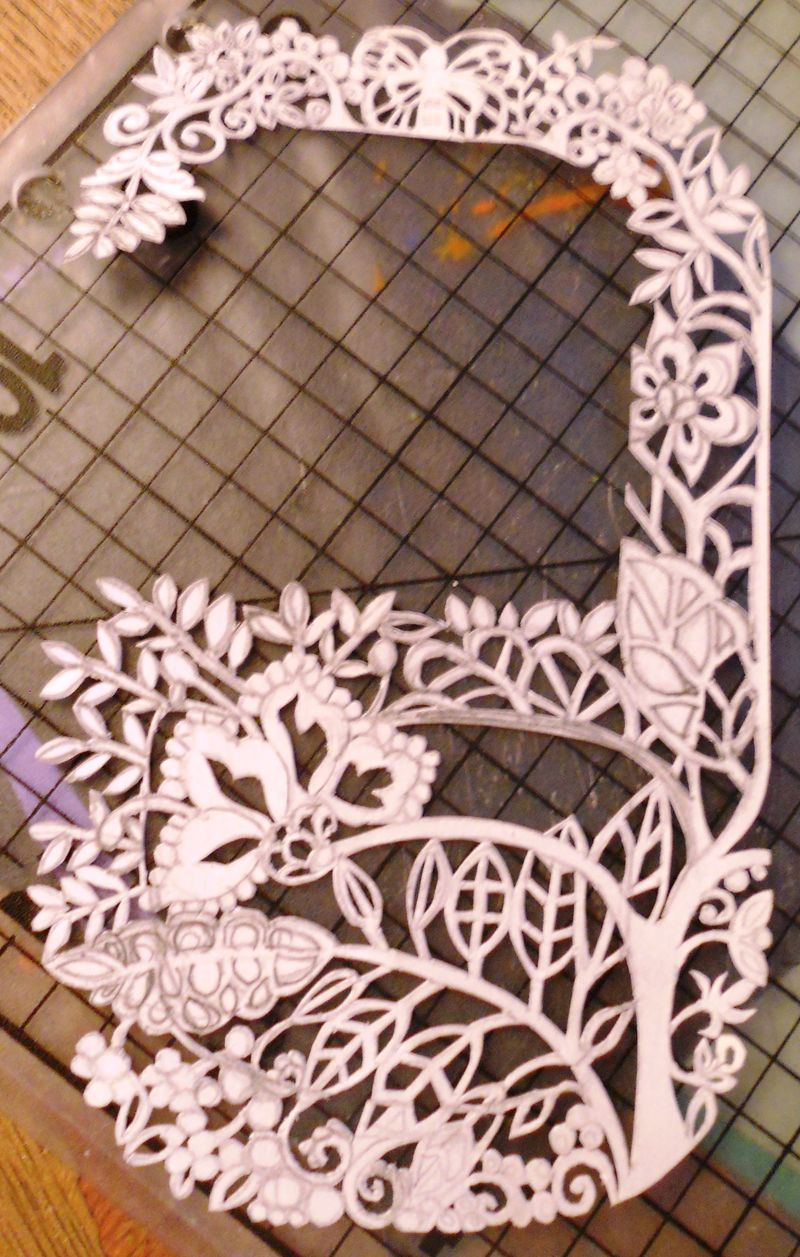 paper art cut of a letter g with botanical motifs and butterflies