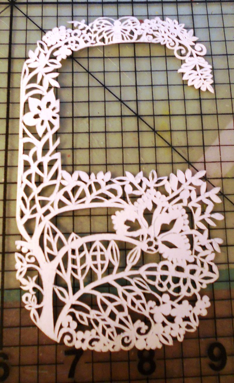 Front view of the paper cut out of a letter G made with botanical motifs and a butterfly on card stock